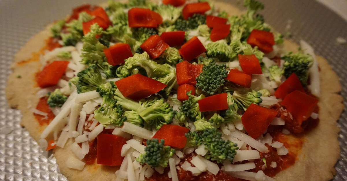 The gluten-free pizza after the crust pre-baked. Loaded down with veggies and goat cheese.