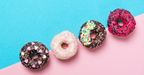 Blue and pink background with multicolored decorated donuts on top