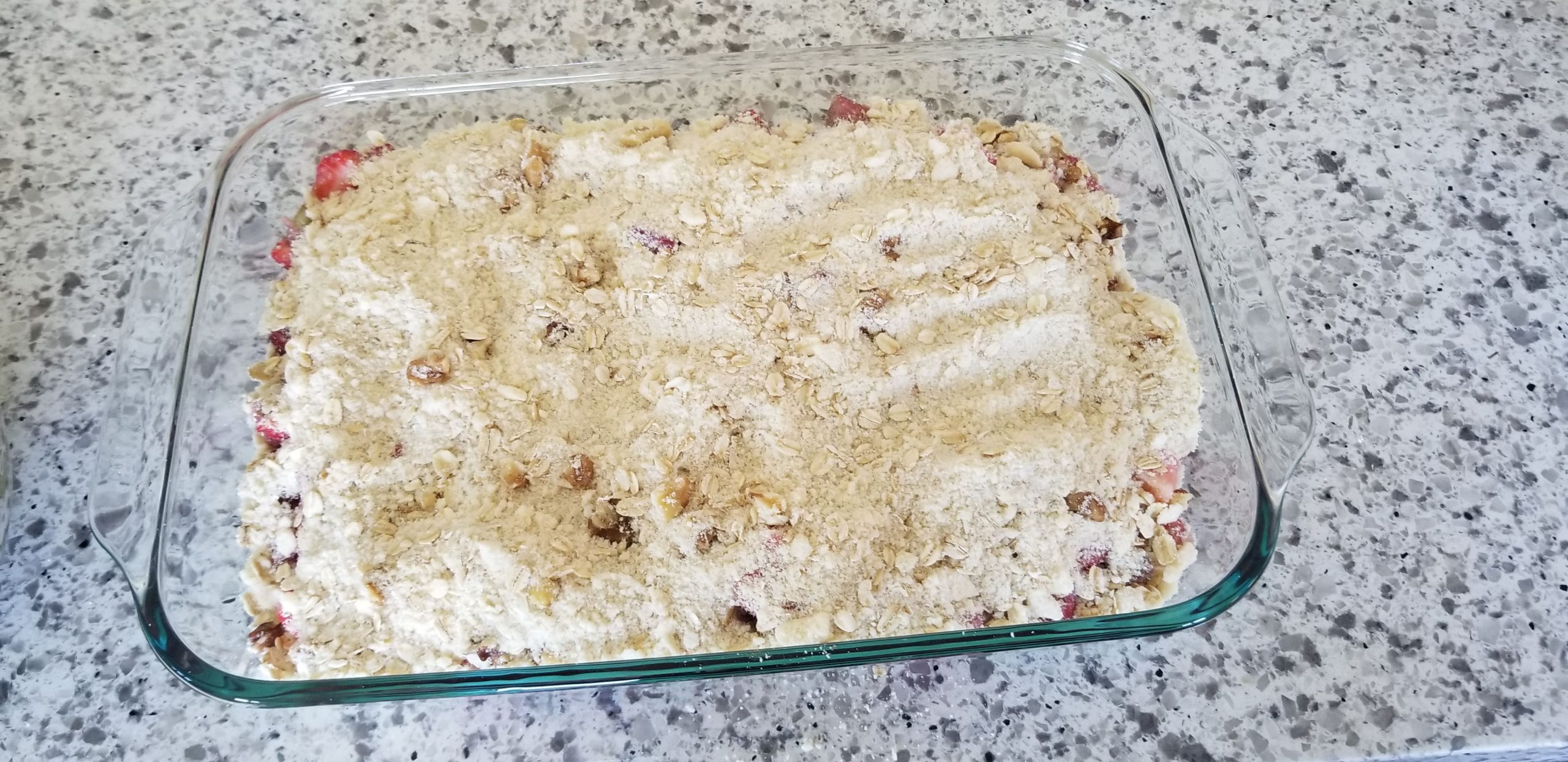 The dairy-free strawberry rhubarb crisp in a casserole dish before it goes in the oven